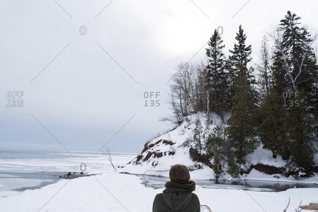 Rear view of woman wearing warm clothing on snow by sea against sky during winter