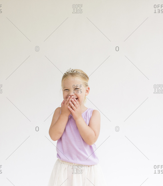 Cheerful shy girl wearing tiara covering mouth while standing against white background