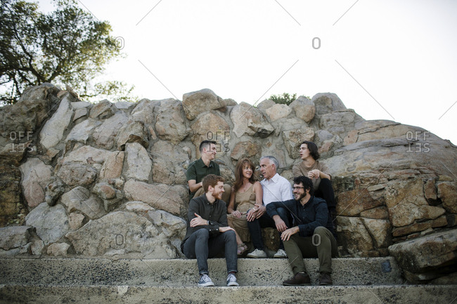 Happy family talking while sitting by rock formations against clear sky at park