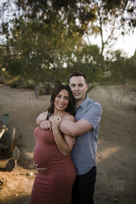 Portrait of husband embracing pregnant wife while standing against trees in park during sunset