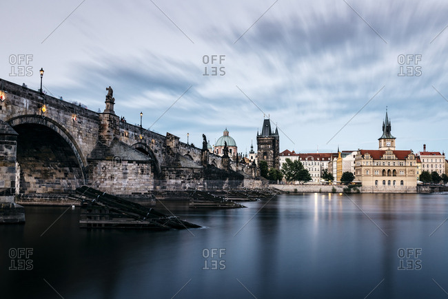 Charles Bridge over Vltava River against cloudy sky