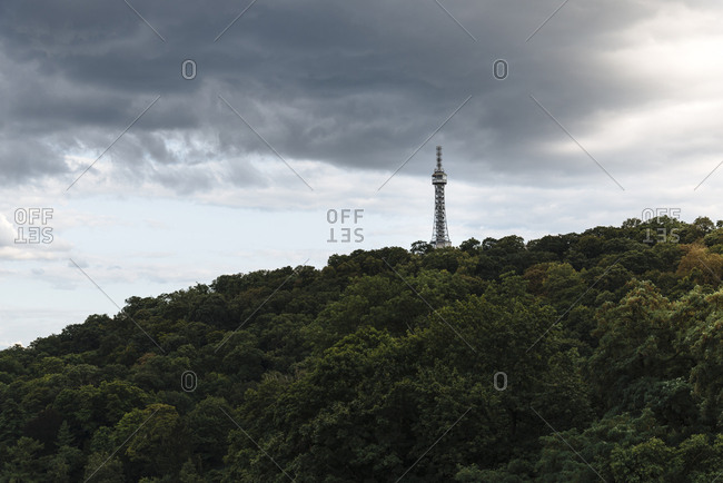 Low angle view of Petrin Lookout Tower on mountain against cloudy sky