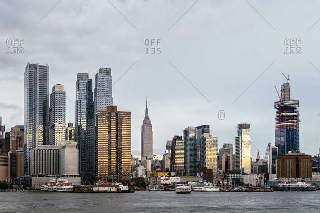 USA, New York, New York - June 23, 2018: Modern buildings in city by river against sky