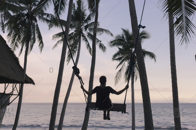 Rear view of young woman swinging on rope swing against coconut palm trees at beach during sunset