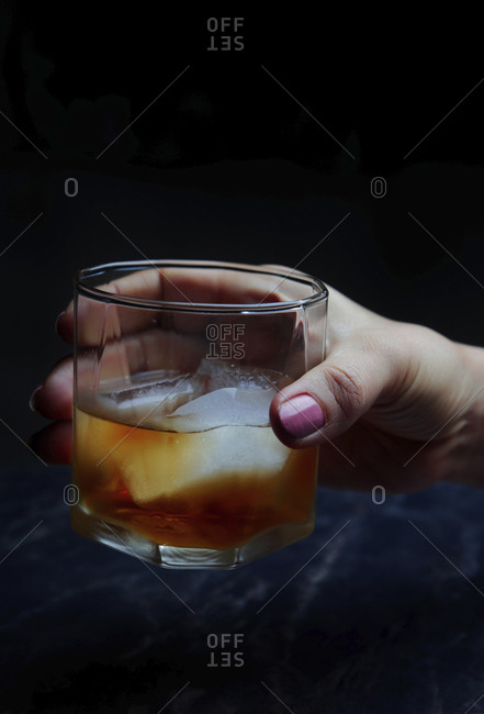 Cropped hand of woman holding whisky against black background