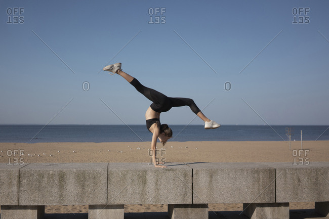 Full length of flexible young woman with legs apart practicing handstand on promenade by sea against sky during sunny day