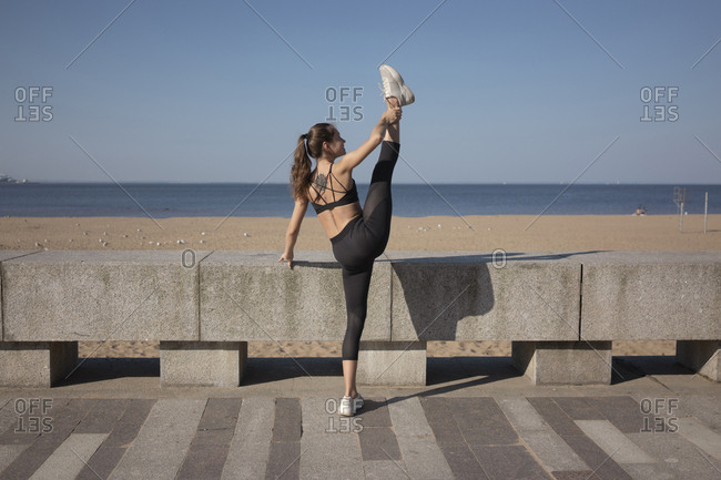 Full length of flexible young woman stretching legs while practicing yoga on promenade by sea against sky during sunny day