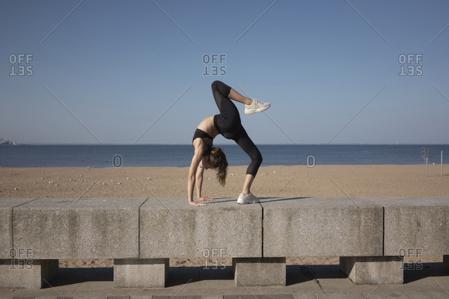 Full length of flexible young woman bending over backwards while practicing yoga on promenade by sea against sky