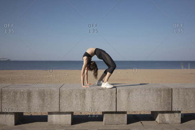 Full length of flexible young woman bending over backwards while practicing yoga on promenade by sea against sky during sunny day