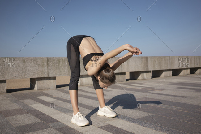 Full length of flexible young woman stretching hands while bending on promenade against sky during sunny day