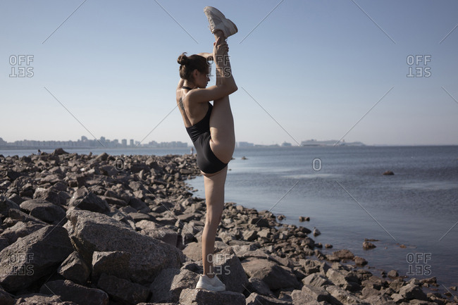 Full length of flexible young woman standing on one leg while practicing yoga on rock at beach against sky during sunny day