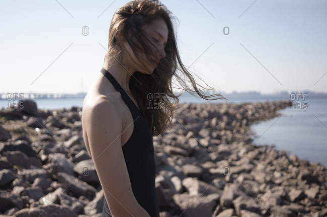 Side view of young woman with tousled hair standing at beach during sunny day