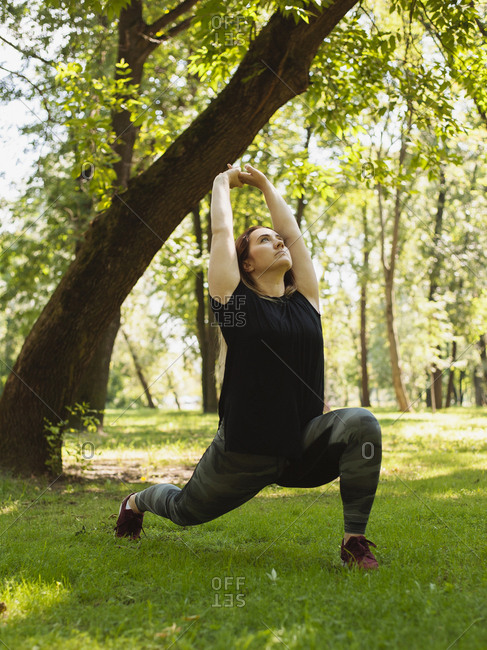 Confident woman with arms raised exercising on grassy field at park