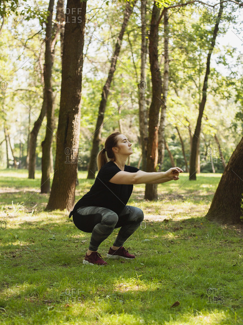 Side view of confident woman with arms outstretched practicing squats on grassy field at park