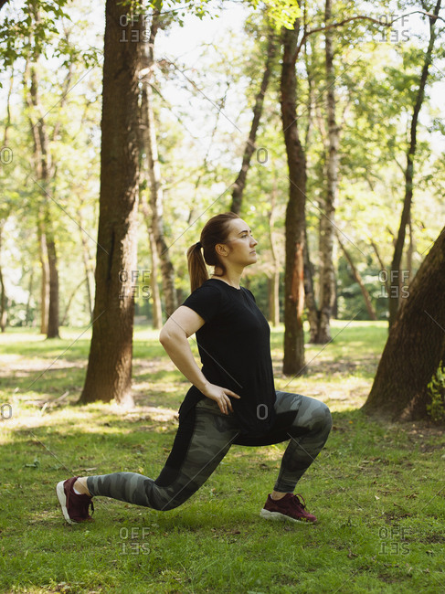 Side view of confident woman looking away while exercising on grassy field at park