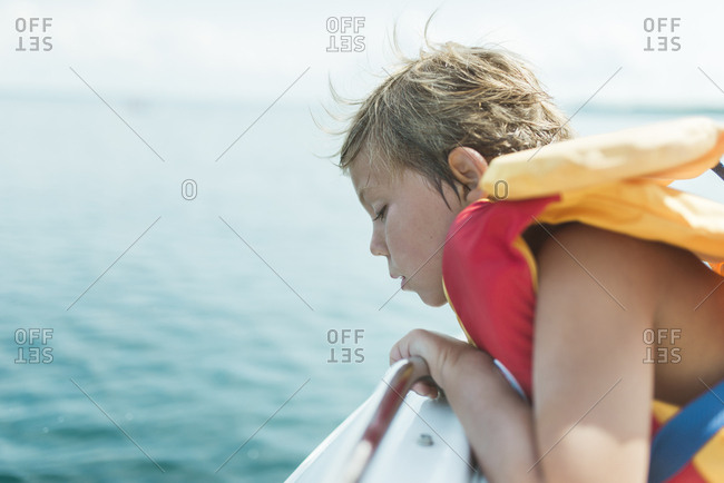 Side view of girl wearing life jacket while sitting in boat on lake