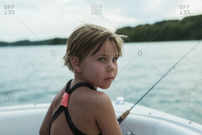Rear view of girl in swimwear looking away while sitting in boat on lake