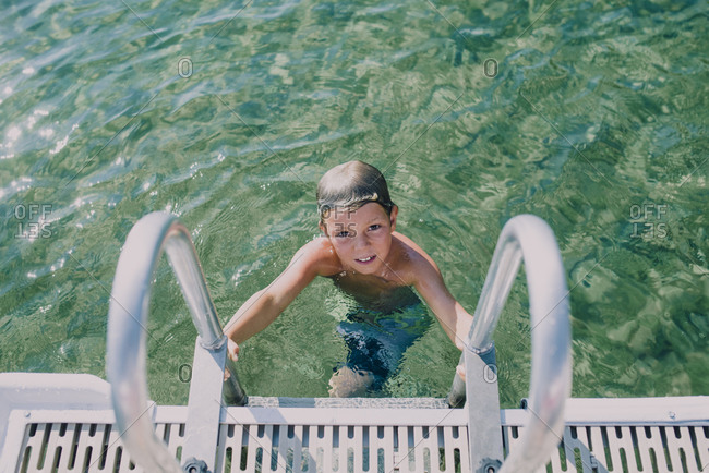High angle portrait of shirtless boy moving up on ladder in lake