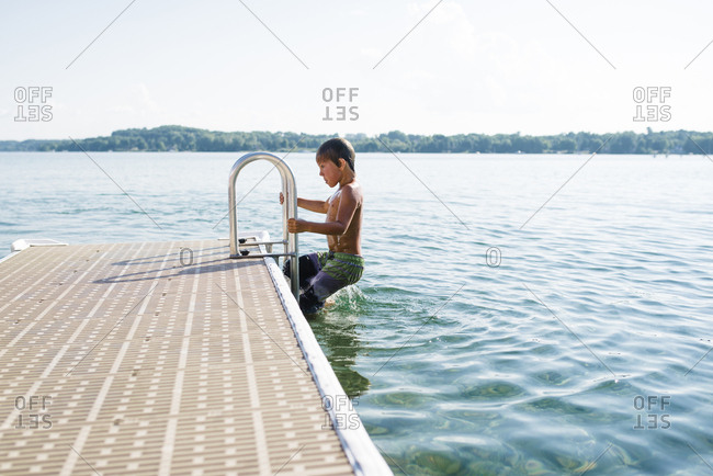Shirtless boy moving up on ladder in lake against sky