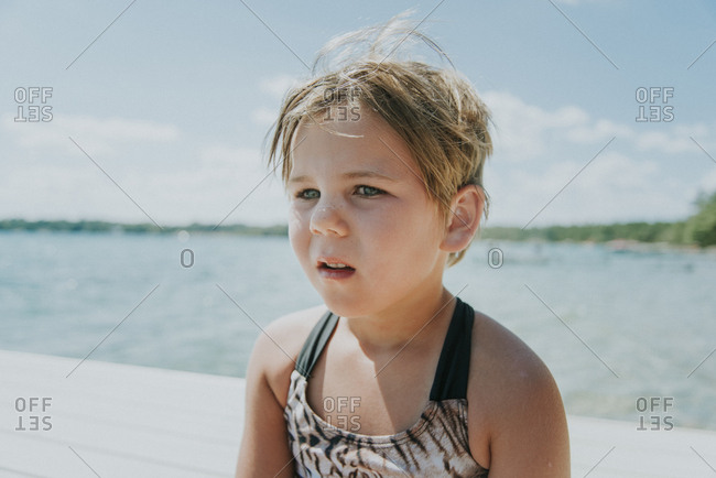 Close-up of thoughtful girl looking away while sitting on pier over lake against sky
