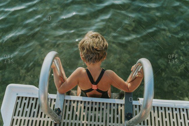 High angle view of girl wearing swimwear while sitting on ladder in lake