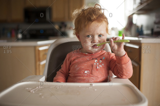 Portrait of cute baby boy with messy face eating food while sitting on high chair at home