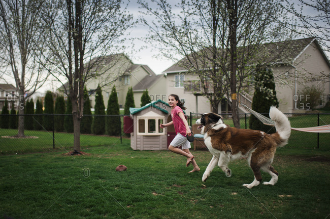 Happy girl playing with dog on grassy field at yard