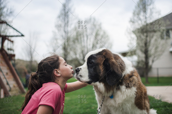 Happy girl kissing dog while sitting on grassy field against sky at yard