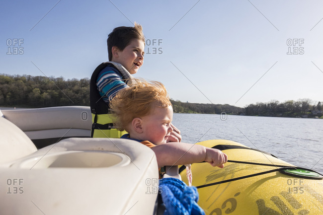 Brothers wearing life jackets while standing in boat on lake against clear sky during sunny day