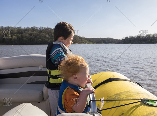 Happy brothers wearing life jackets while standing in boat on lake against clear sky during sunny day