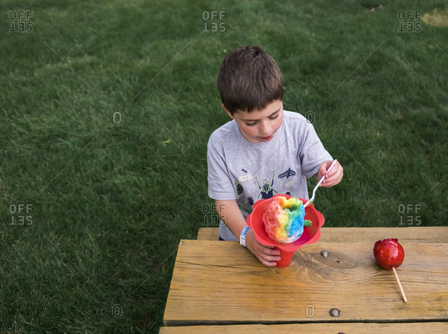 High angle view of boy eating flavored ice while sitting on bench at park