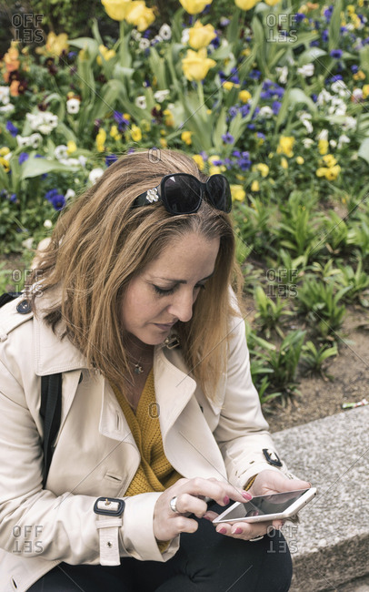 High angle view of businesswoman using mobile phone while sitting by plants on retaining wall
