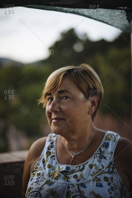 Close-up portrait of senior woman with short hair standing on building terrace during sunset