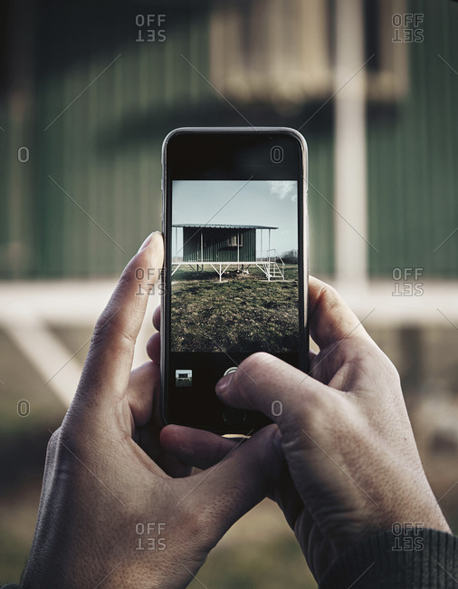 Cropped hands of man photographing house with mobile phone
