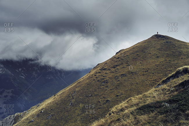 Distant view of man standing on Balkan Mountains against cloudy sky