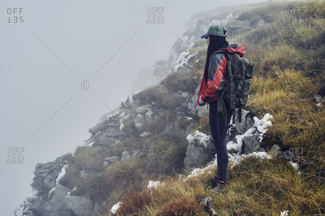 Side view of female hiker standing on Balkan Mountains during foggy weather