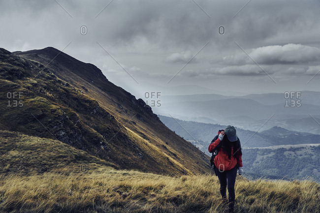 Female hiker standing on Balkan Mountains against cloudy sky
