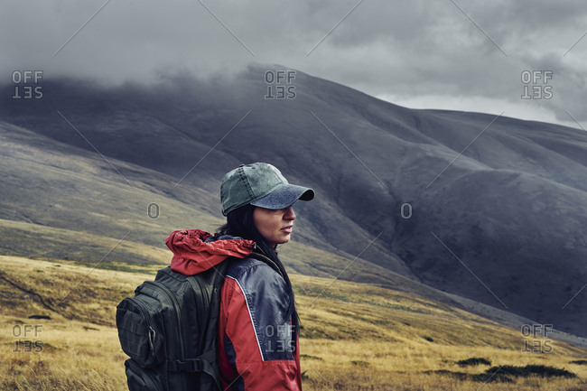 Side view of female hiker with backpack standing on Balkan Mountains against cloudy sky