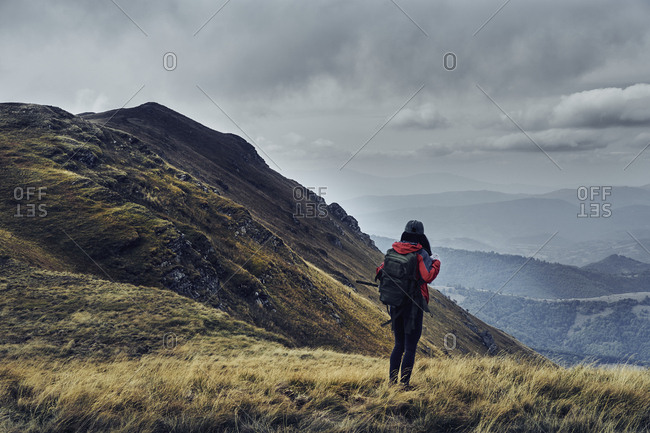 Rear view of female hiker with backpack standing on Balkan Mountains against cloudy sky
