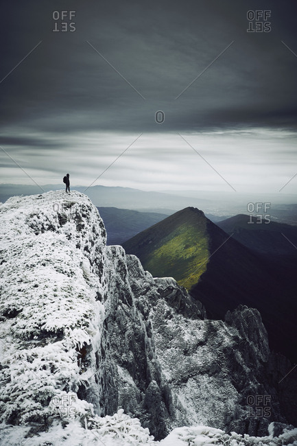 Mid distance view of woman standing on snow covered mountain against cloudy sky