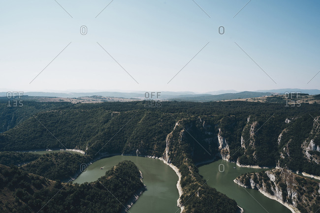 Scenic view of lake by mountains against clear sky during sunny day