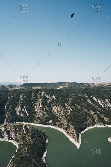 Scenic view of lake by mountains against clear blue sky during sunny day