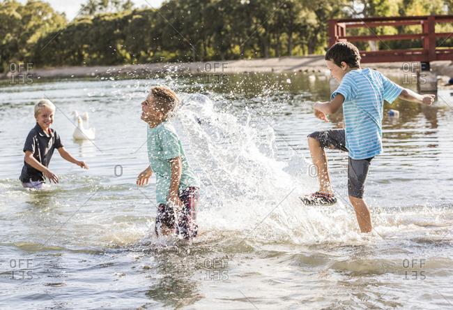 Happy friends splashing water in lake