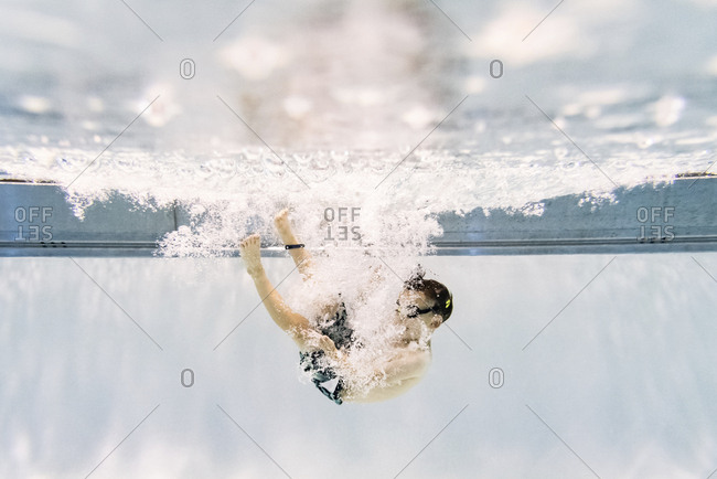 Full length of shirtless boy swimming underwater in pool