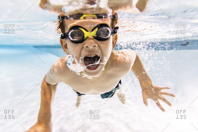 Portrait of shirtless boy with mouth open swimming in pool