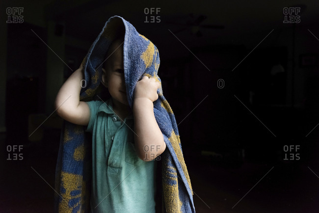 Portrait of cute baby boy playing with towel while standing in darkroom at home
