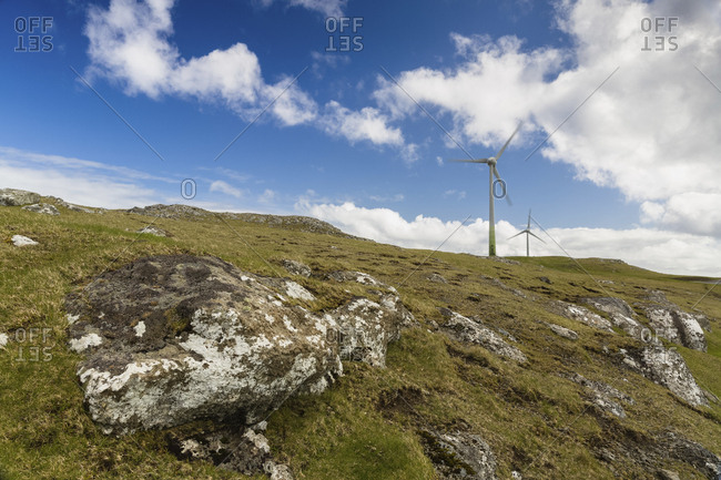 Low angle view of windmills on hill against blue sky