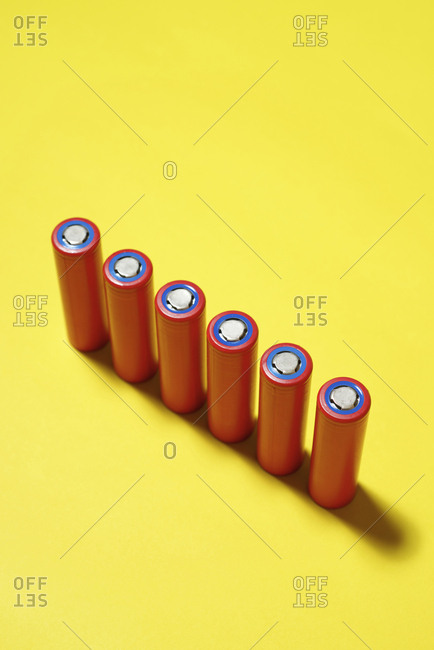 High angle view of batteries on yellow background