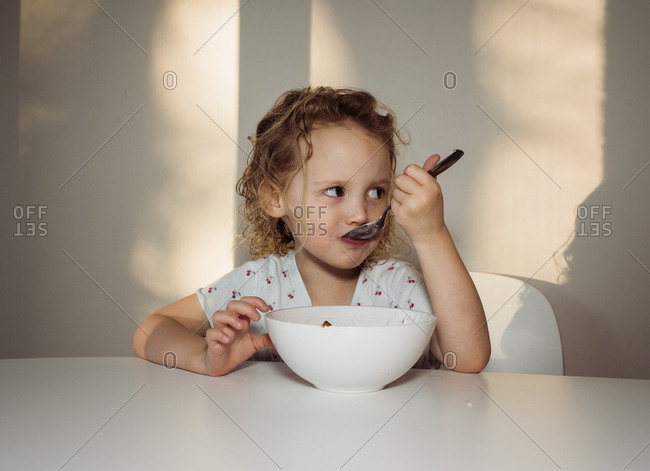 Girl looking away while eating food on table at home