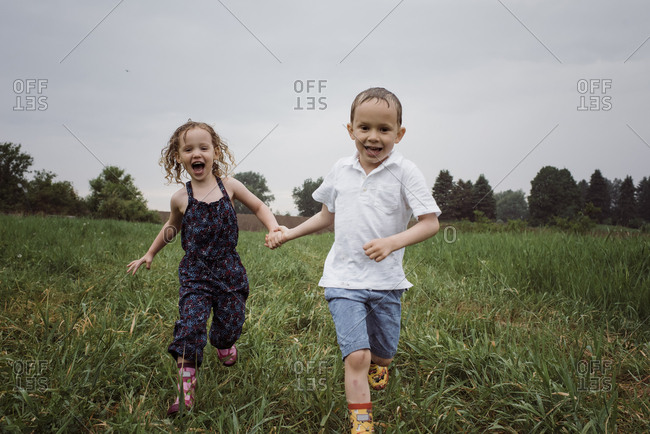 Portrait of happy wet siblings holding hands while running on grassy field against sky at park during rainy season